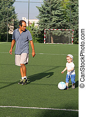 Happy family, boy playing football with dad
