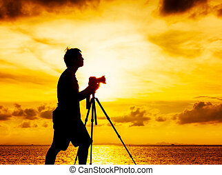 Silhouette of photographer at sunset