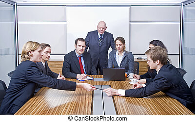 Board Meeting - Seven people in a cubicle, preparing for a...