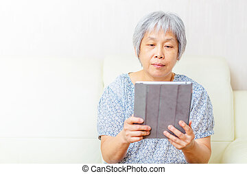 Asian old woman using tablet