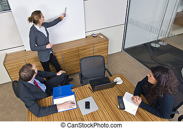 Business presentation - Three young business associates in a...