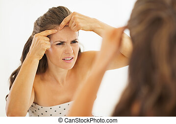 Concerned young woman squeezing acne in bathroom
