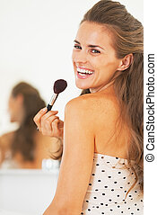 Portrait of smiling woman with makeup brush in bathroom