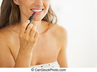 Closeup on woman applying lipstick in bathroom