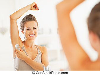 Smiling young woman applying roller deodorant on underarm in...