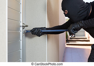 Thief with a bar of iron in the hand to open a door