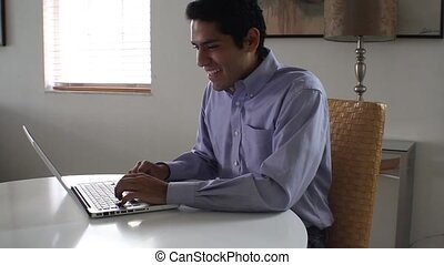 Businessman laughing while chatting on a laptop.