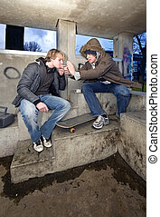 Smoking shelter - Two adolescent youths in a suburbian area,...