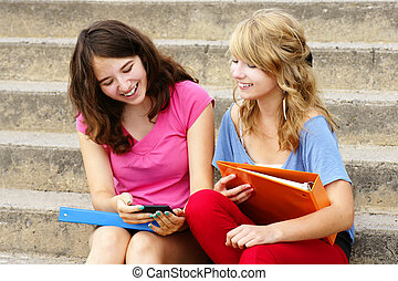 Teenagers laughing at cell phone - Two teenager girls...