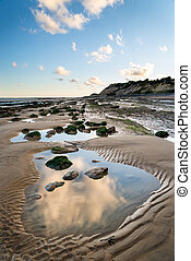 Summer landscape with rocks on beach during late evening and...