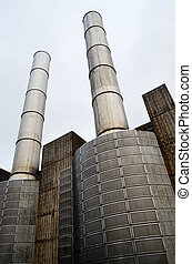 industrial building and two metal chimney against the gray...