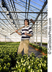 Horticulture - A man with a broom in his hand giving a...