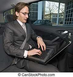 Working in a taxi - A businessman working in the backseat of...