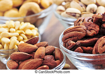 Bowls of assorted nuts - Many glass bowls of almonds walnuts...