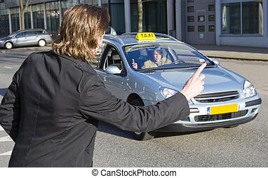 Hauling a taxi - A businessman raising his hand to haul a...