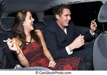 Backseat fun - A young couple laughing in the backseat of a...