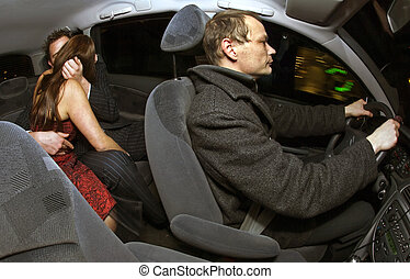Backseat Kissing - A couple kissing after a night out in the...