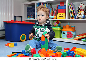 A baby boy playing with plastic blocks on the floor