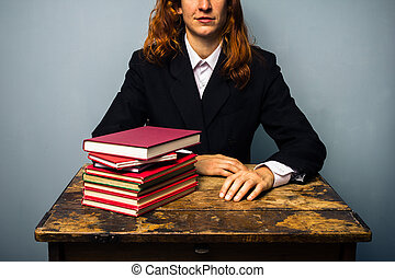 Businesswoman with stack of books