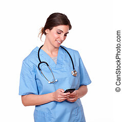 Charming nurse smiling while sending a text - Portrait of a...