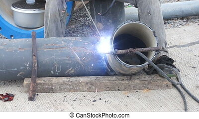 Welder uses torch for welding pipe metal on site