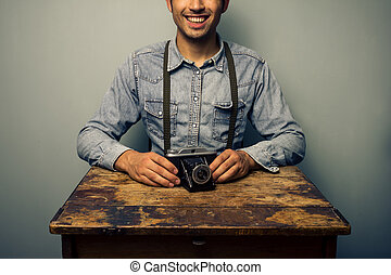 Trendy man with vintage camera at old desk
