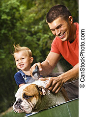 Family giving dog a bath. - Caucasian father and toddler son...
