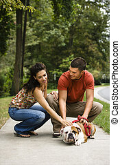 Couple petting dog - Caucasian mid adult couple petting...