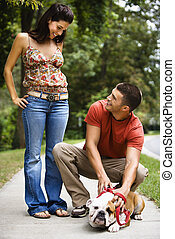 Couple petting dog - Caucasian mid adult couple with English...