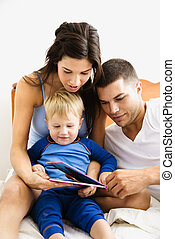 Family reading - Caucasian parents and toddler son reading...