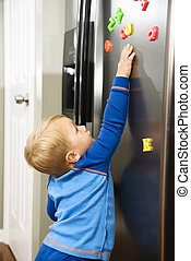 Child playing. - Caucasian toddler boy reaching for magnets...