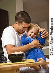 Dad tickling son. - Caucasian man tickling toddler son in...