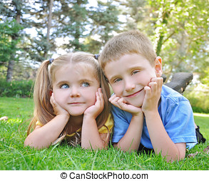 Happy Children Smiling in Green Grass