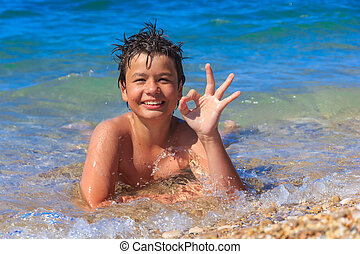 Happy young boy on the sea beach OK - happy laughing boy of...