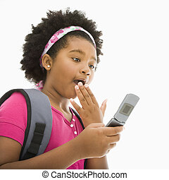 Surprised girl on phone - African American girl with...