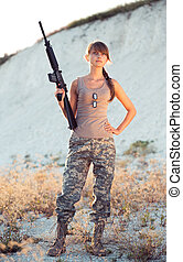 Young beautiful female soldier dressed in a camouflage with...