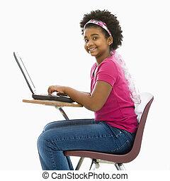 Schoolgirl on laptop - African American girl sitting in...