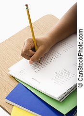 Child doing homework - Hand of African American girl at...