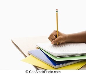 Child doing schoolwork. - Hand of African American girl at...