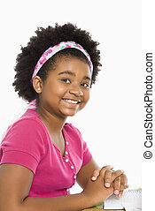 Preteen girl - African American girl sitting in school desk...