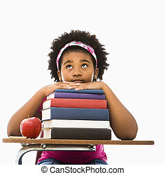 Girl with stack of books. - African American girl sitting in...