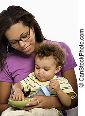 Mother feeding child. - African American mid adult mom...
