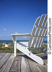 Chair on beach deck - Empty white adirondack chair on wooden...