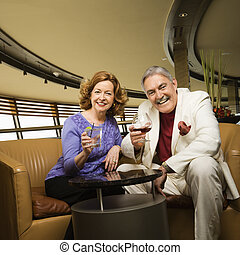 Couple having drinks - Mature Caucasian couple sitting in...