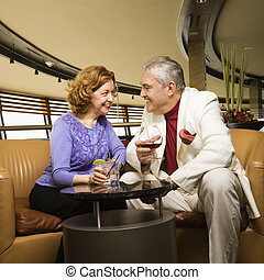 Mature couple - Mature Caucasian couple sitting in bar...