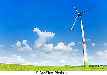Wind turbine in the field with clouds in the sky on bright...