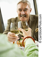 Mature couple toasting - Mature couple dining and toasting...