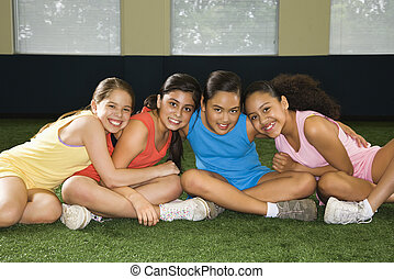 Group smiling girls - Four multiethnic girls sitting with...