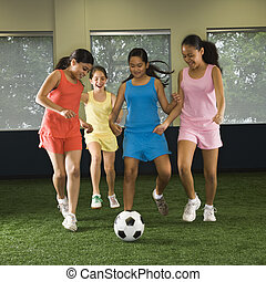 Girls playing soccer - Four multiethnic girls playing soccer...