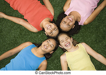 Laughing girls. - Above view of four girls lying on...